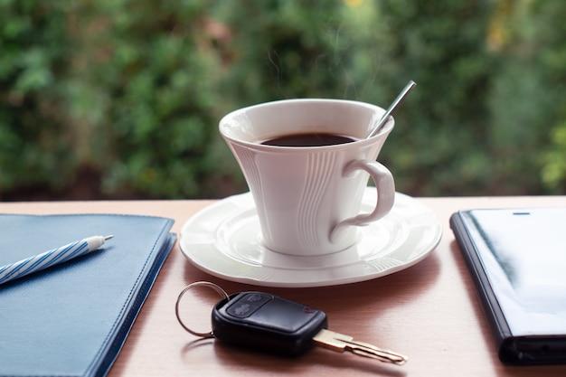 キーノートとカフェでスマートフォンとホットブラックコーヒー