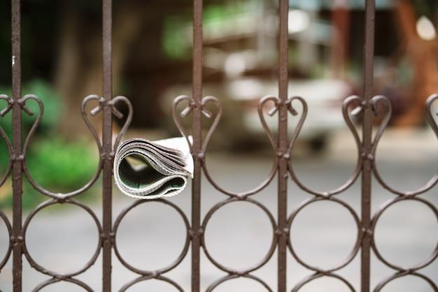 新聞の配達がフェンスに掛かる