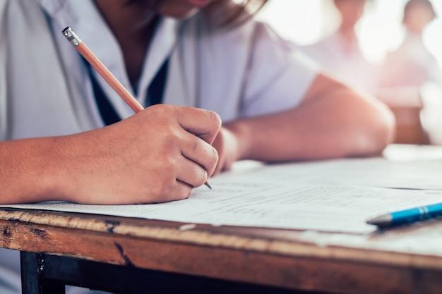 鉛筆を保持し、期末試験を書く学生へのクローズアップ