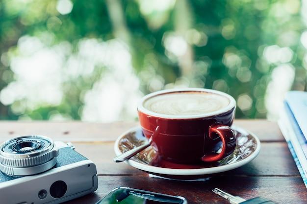 Чашка горячего кофе, пленочная камера, книги, смартфон и ключи на деревянной тарелке