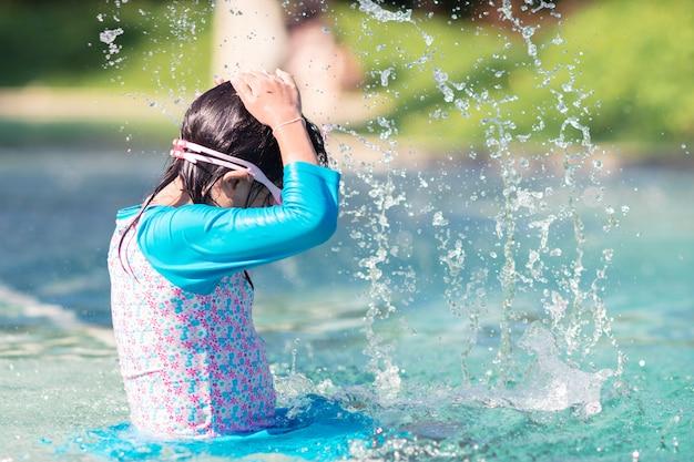 スプラッシュ水とプールでアジアの女の子を着てゴーグルの笑みを浮かべてください。