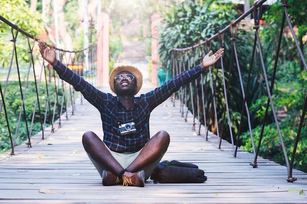 橋の上に座っているアフリカ人旅行者