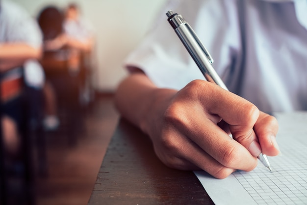 生徒の手が試験を受けて教室で答えを書いている