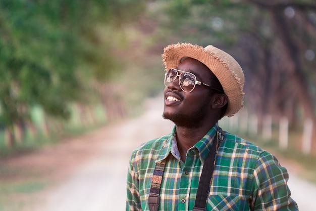 Африканский человек путешественник улыбается с зеленым фоном природы