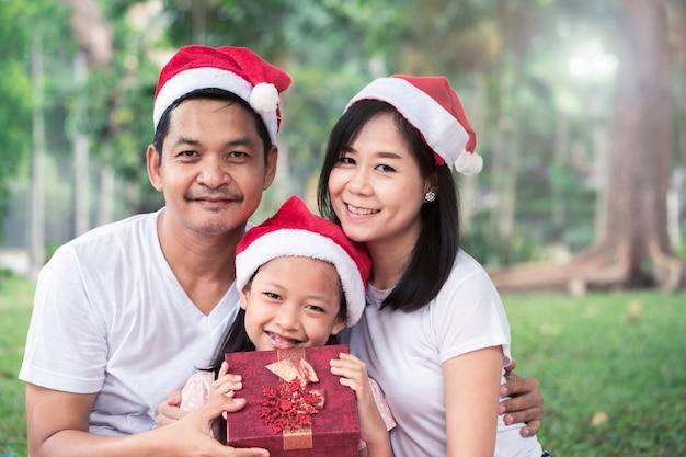 アジアの家族の父親の母親と娘は、メリークリスマスで抱擁