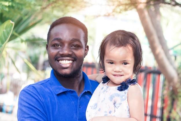 笑顔のアフリカ人は愛と幸せでアジアの子供の女の子を運んでいます。