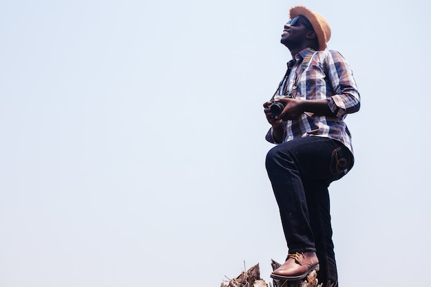 アフリカの男性カメラマン乾いた木にサングラスとフィルムカメラを持って立っています。