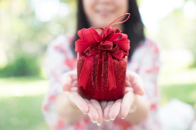 リボンで小さな贈り物をしている女性の手を笑顔。選択フォーカス。