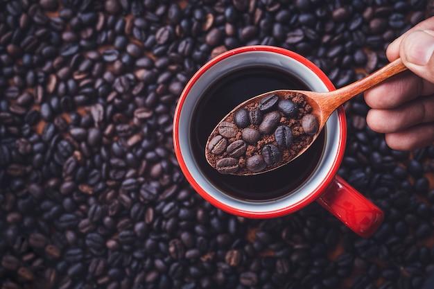 Кофейные зерна на деревянной ложкой над красной чашкой с черным кофе