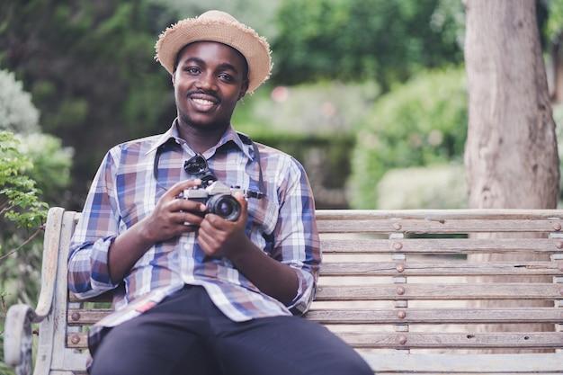 緑の自然な背景を持つカメラを保持しているアフリカ人男性旅行者