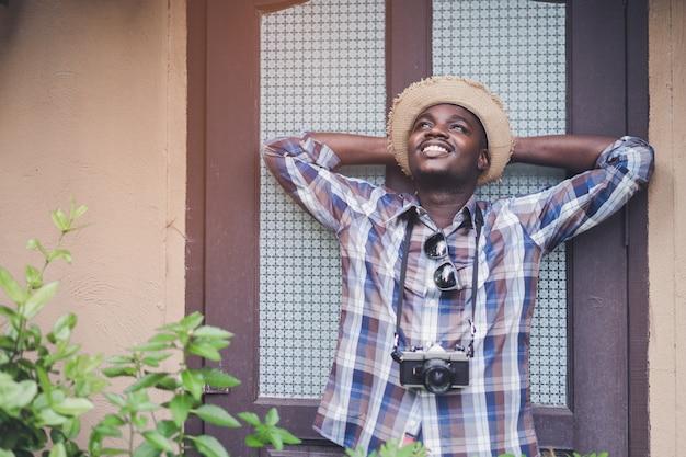 ビンテージウィンドウの背景を持つカメラを保持しているアフリカ人男性旅行者