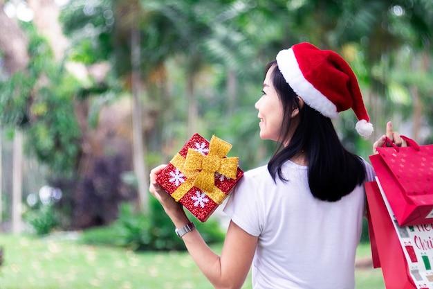 アジアの女性が贈り物を持っていて、袋は服装のイヤリング
