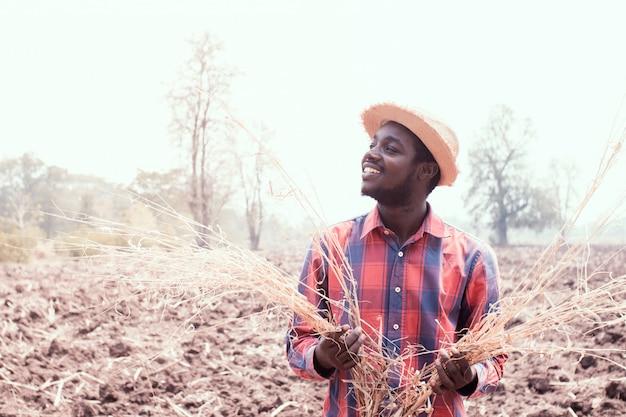 Портрет африканского человека фермера стоя на сухом поле