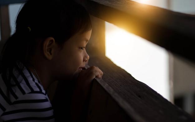 アジアの子少女の笑顔と外を見ています。