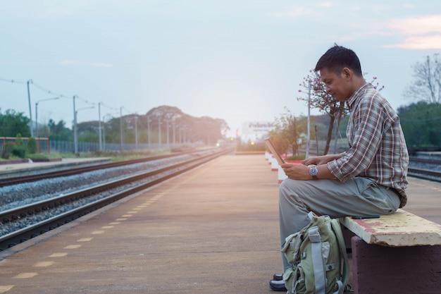 Улыбка человек с помощью портативного компьютера в ожидании поезда.