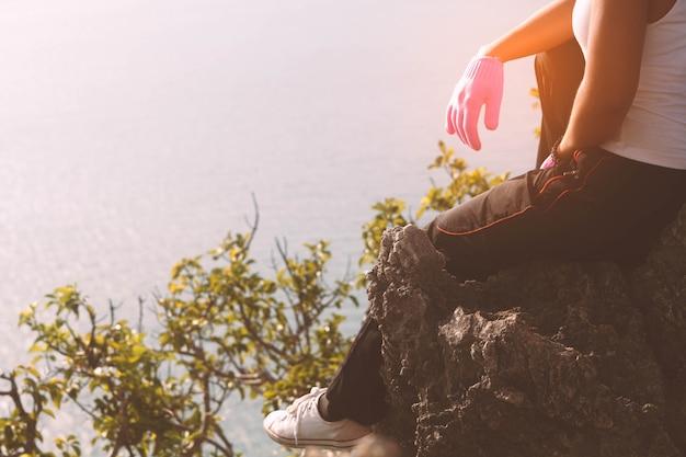 女性登山家は丘の上に座っています。