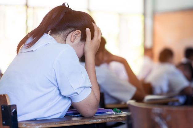 学校の教室でストレスで試験を受ける学生。