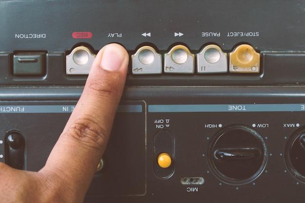 ラジオカセットプレーヤー、ビンテージスタイルを再生するために指を閉じます。