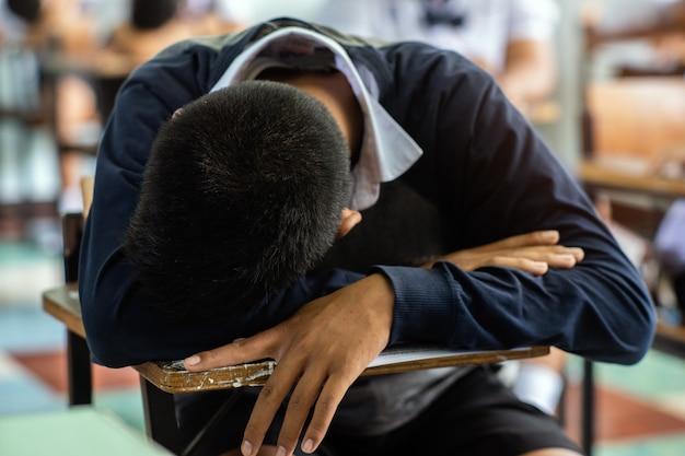 椅子で寝ている生徒、試験後の答えシートは教室で練習します