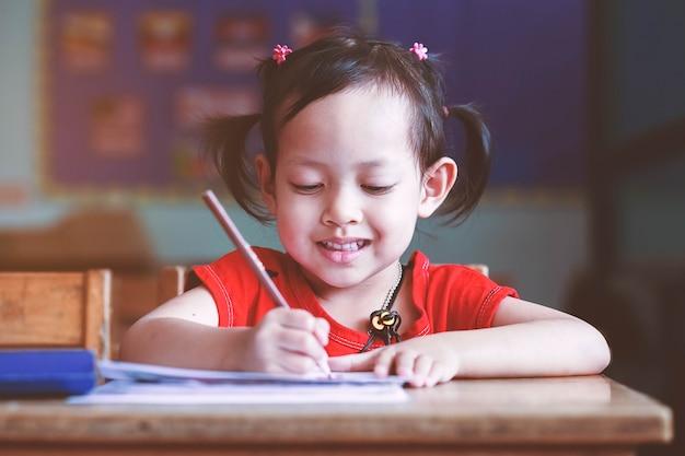 笑顔の子供女の子が机の上に書きます。