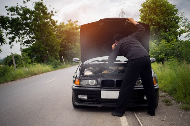 ストレスの実業家がスマートフォンを使用して壊れた車、エンジンを開くと喫煙を探しています。