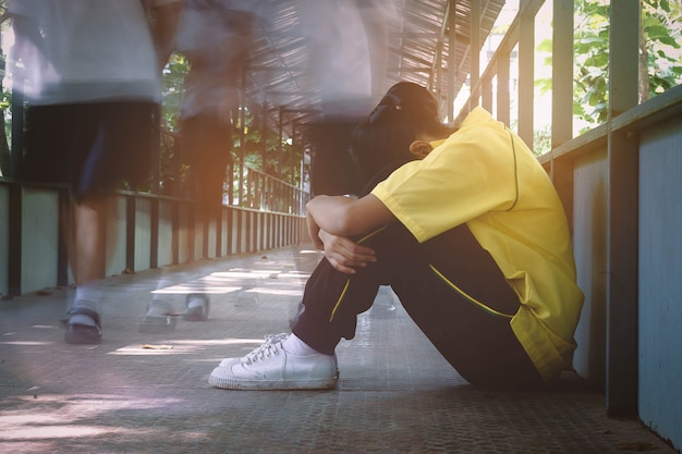 橋の上に座っているうつ病の学生。