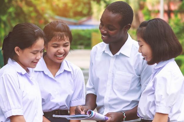 幸せなアジアの学生を教えるアフリカの先生。