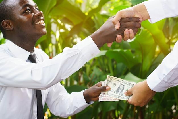 アメリカとアジアのビジネスマンのお金とハンドシェーク。フォーカスを選択します。