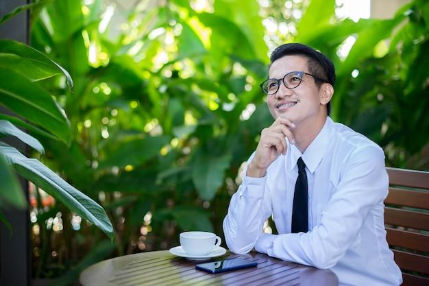 Бизнес азиатских человек планирует свое будущее. он сидит и улыбается на зеленом фоне природы.