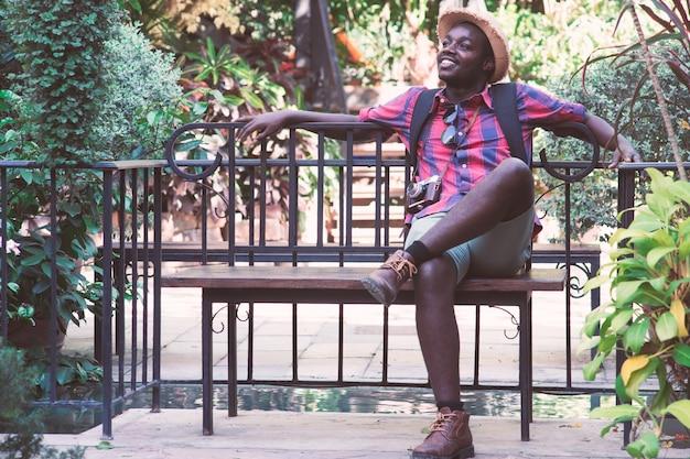 アフリカの旅行者の男は笑顔と幸せでテーブルに座っている。