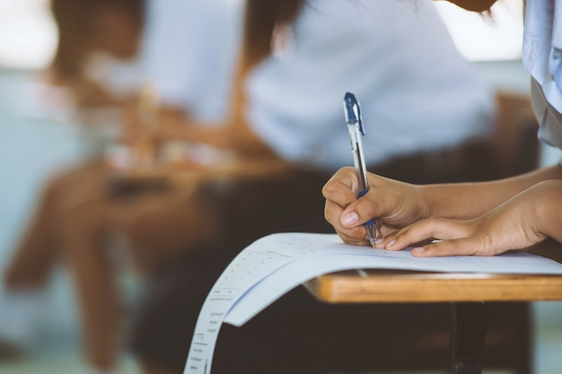 学校で教室で試験またはテストするために制服の学生の手を書くのクローズアップ。