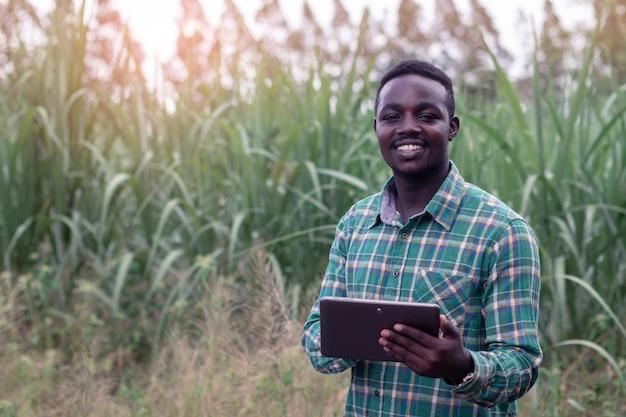 アフリカの農家がタブレットを保持していると緑の農場に立つ