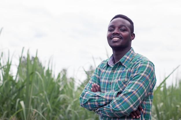 緑の農場で立っている帽子を持つアフリカの農家