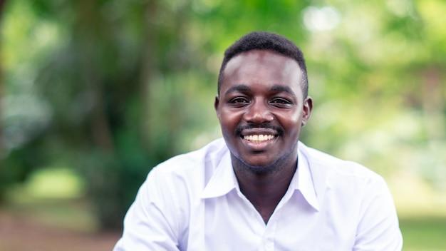 笑みを浮かべて、緑の木が外に座っている白いシャツのアフリカのビジネス人