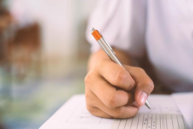 手でペンを持って試験をしている学生は、ストレスのある教室で解答用紙練習に答えます。
