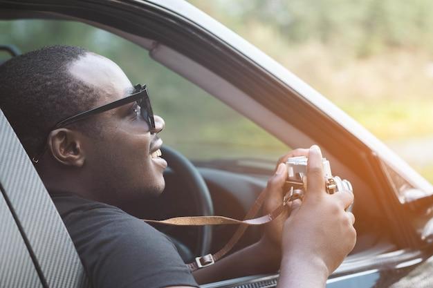 アフリカ人ドライバーのフィルムカメラを持って、開いているフロントウィンドウが付いている車に坐っている間笑顔
