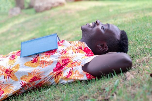 開かれた本と草の上に横たわっているアフリカの旅行者男
