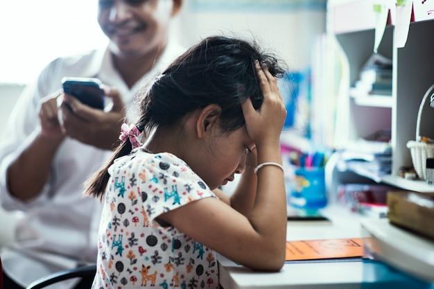 彼女の頭を両手で座っている子供の女の子を強調しました。彼女の父親は興味がなかったので
