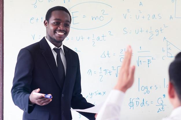 教室で科学を教えるアフリカの外国人教師。