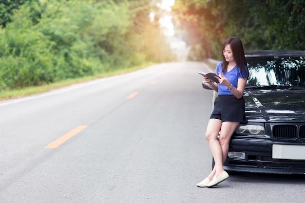 立っていると彼女の車で本を読んで笑顔の女性旅行者