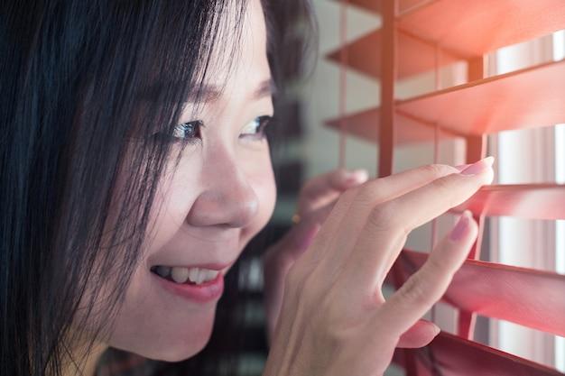 アジアの女性は窓のブラインドで離れて手します。
