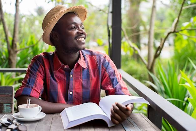コーヒー、キー、スマートフォン、緑の自然な背景で本を読んでアフリカ人。