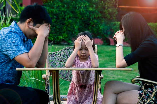 アジアの小さな娘のストレスと父親と母親と頭痛。熱狂的な問題の概念。