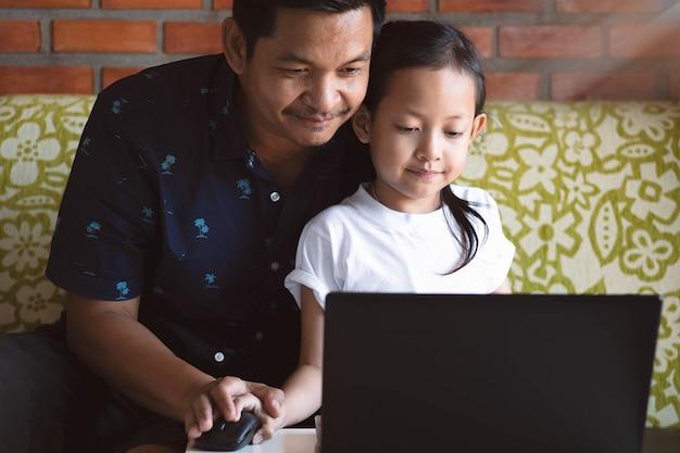 娘と父親の学習と自宅でコンピューターのラップトップを再生
