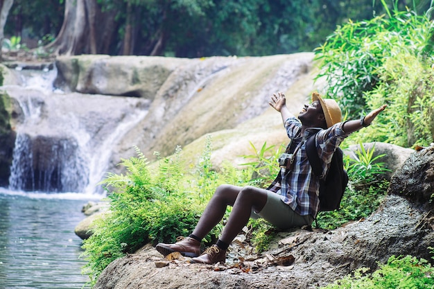 アフリカ人旅行者のフィルムカメラを保持し、滝でリラックスした自由