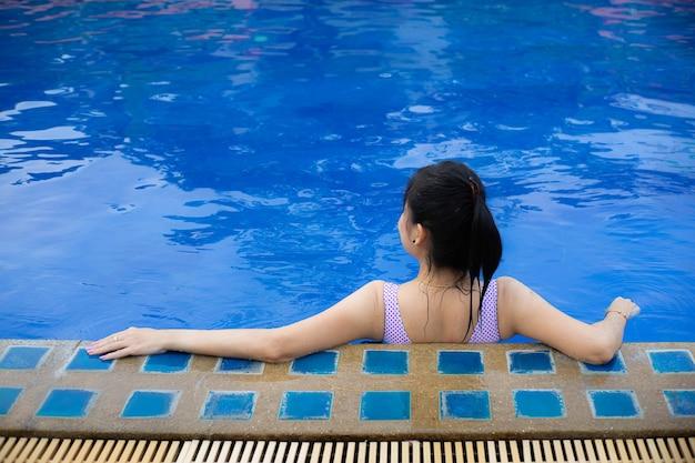 スイミングプールでリラックスした女性