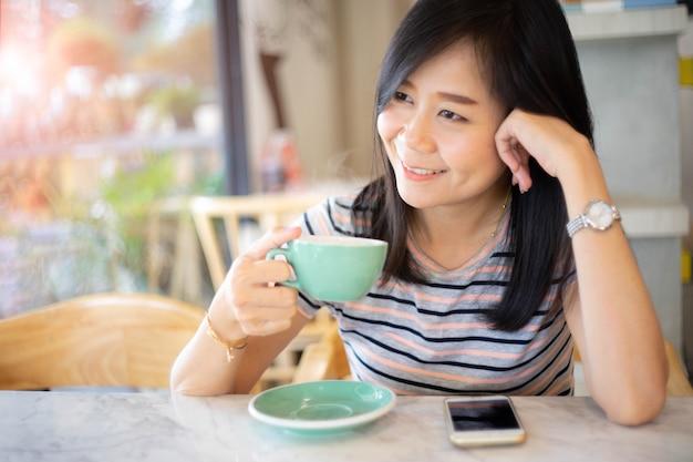 アジアの女性のコーヒーショップで笑顔