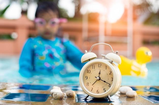 スイミングゴーグルを身に着けている子供とスイミングプールでレトロな目覚まし時計。