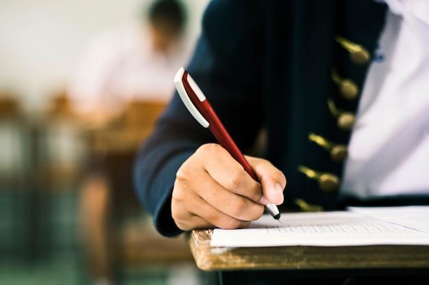ストレスのある学校の教室で試験解答用紙を書いたり読んだりする生徒を閉じます。