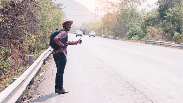 高速道路の道を歩いてバックパックを運ぶアフリカ人旅行。観光日の概念